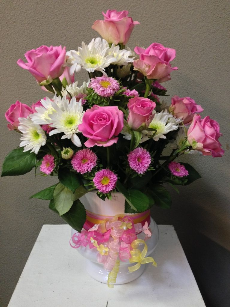 A birthday arrangement of pink roses and asters mixed with mums