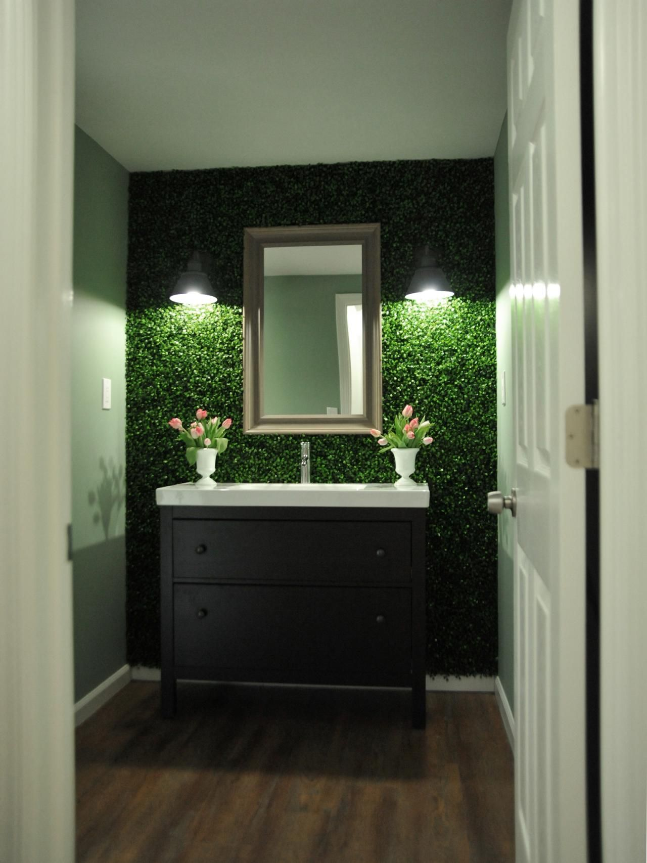 Panels of faux boxwood leaves offer an earthy feel to the for Bathroom decor green walls
