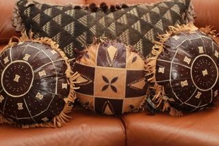 Unusually large, rectangular Kuba Cloth Pillow shown with three one of a kind, vintage round leather pillows. All pillows are stuffed with feathers. The Kuba Cloth Pillow $360, leather Pillows are $250, the set $550. Immediate delivery.