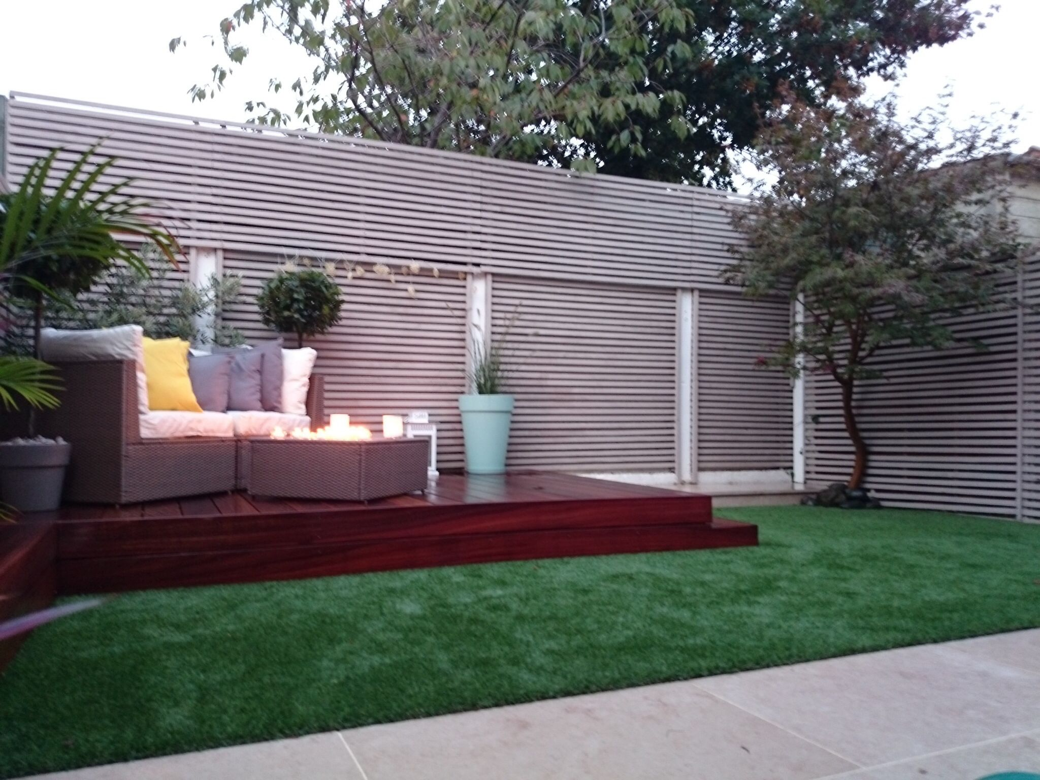 Garden Overview With Painted Trellis, Limestone Paving, Artificial Grass,& Deck