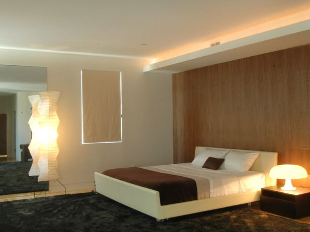 . A wood wall is the backdrop for this modern bedroom  Cove lighting