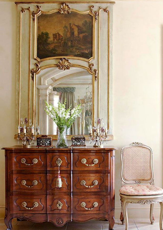 The focal point of this vintage style interior is definitely the gold framed mirror featuring a painted vignette. A 3 drawer dresser w/ flowers on top sits below the mirror.