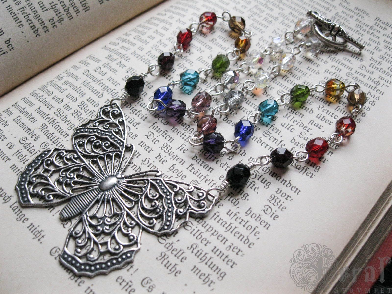 A beautiful filigree butterfly rendered in brass and plated in sterling silver hangs from a simple hand wrapped rosary style link chain of many colours-- a muted, darkened rainbow which corresponds to the 7 chakras in the body. A Victorian-inspired filigree clasp completes the piece.Â