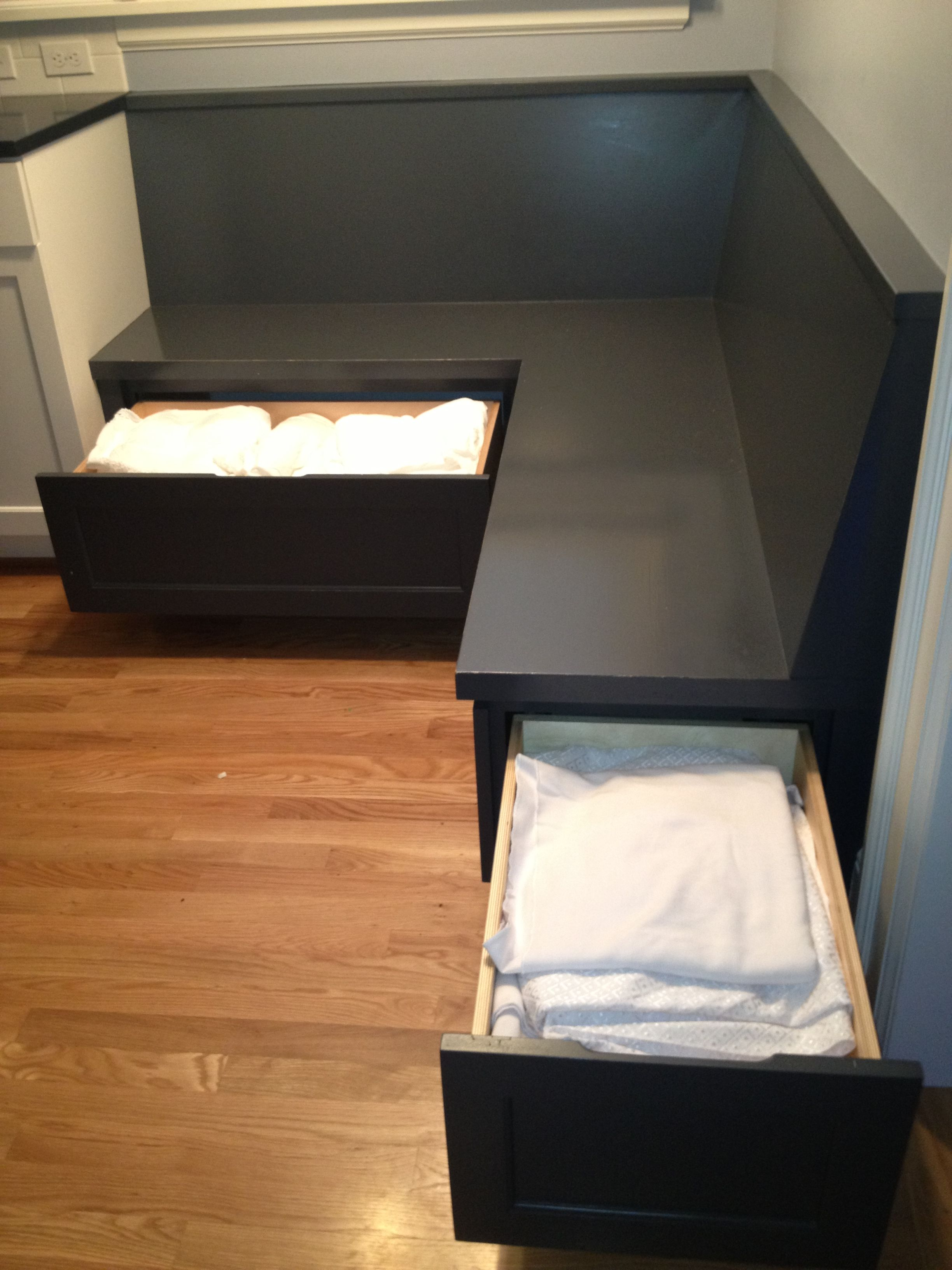 Storage for table linens under custom built in corner for Banquette bench