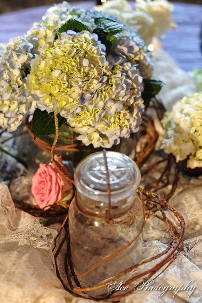 use grape vine around low vases with big flowers and jars- some with candles on lace or burlap