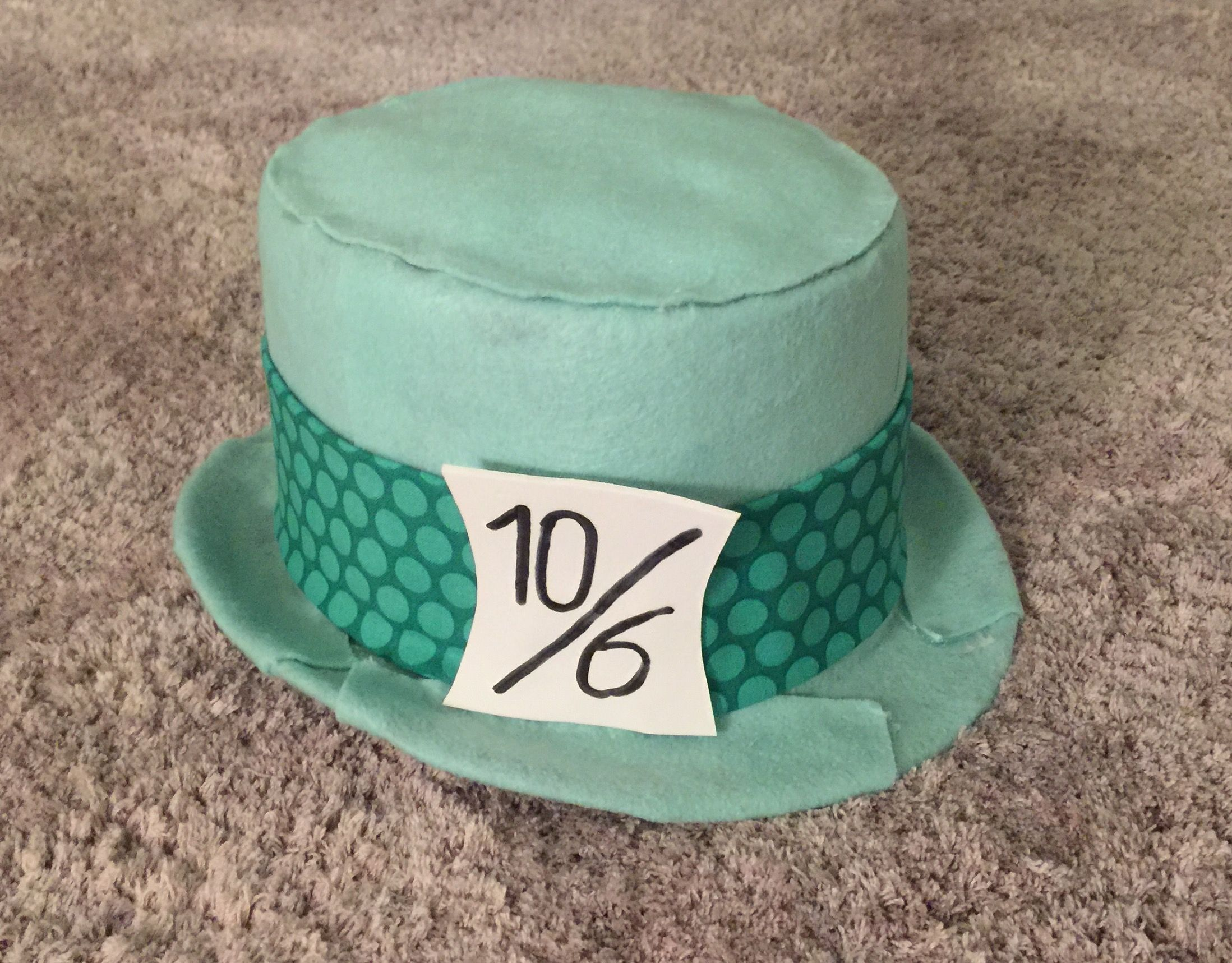 My attempt at a Mad Hatter Hat 1951 version I used the Disney Mickey ears groom hat, took off the ears and used a mint green felt and found some interesting fabric for the band then used styrofoam for the 10/6 tag Ears can be kept or removed