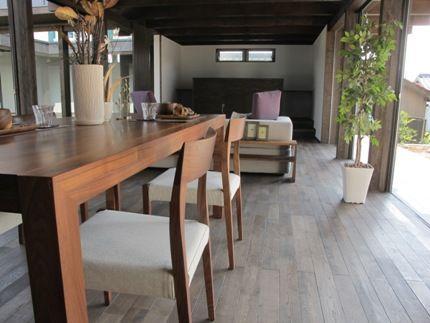 グレー色のくすんだ床材にウォールナット無垢材の家具を合わせた