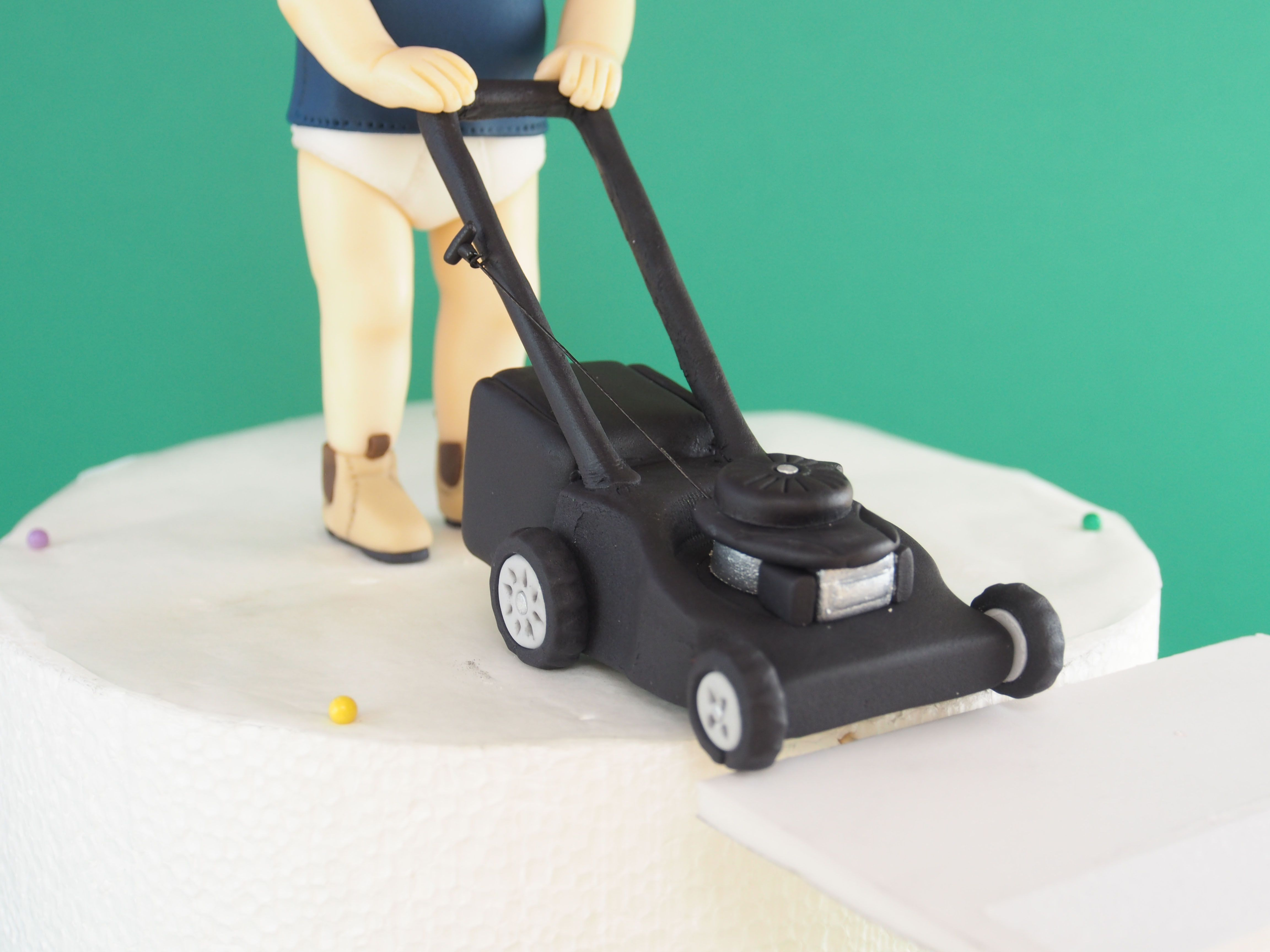 Man and lawnmower cake topper