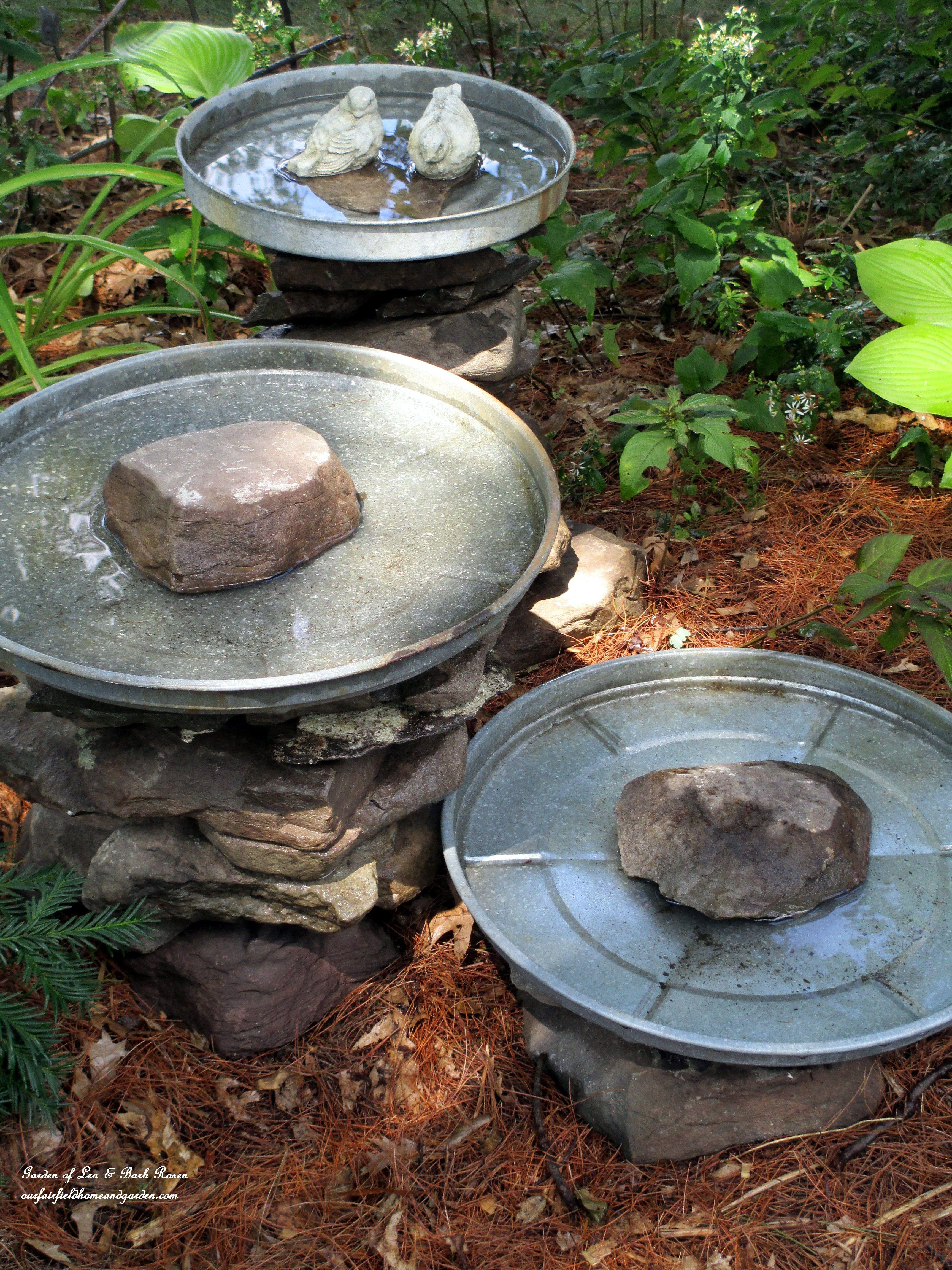 stacked stone birdbaths using garage sale trash can lids garden
