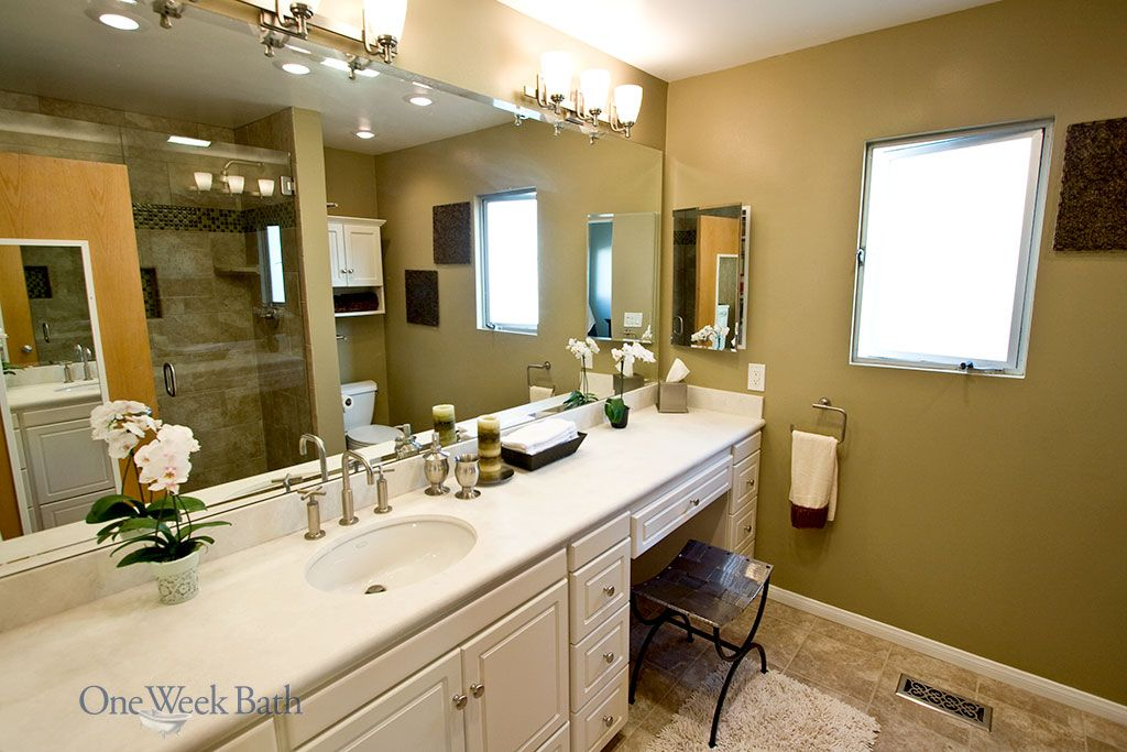 One Week Bath renovated this transitional style bathroom, which features upward facing light fixtures. Our transitional style bathroom remodel includes a vanity with a built-in dressing table. This transitional bathroom design features both modern and traditional bathroom styles. #OneWeekBath #Transitional #Bathroom