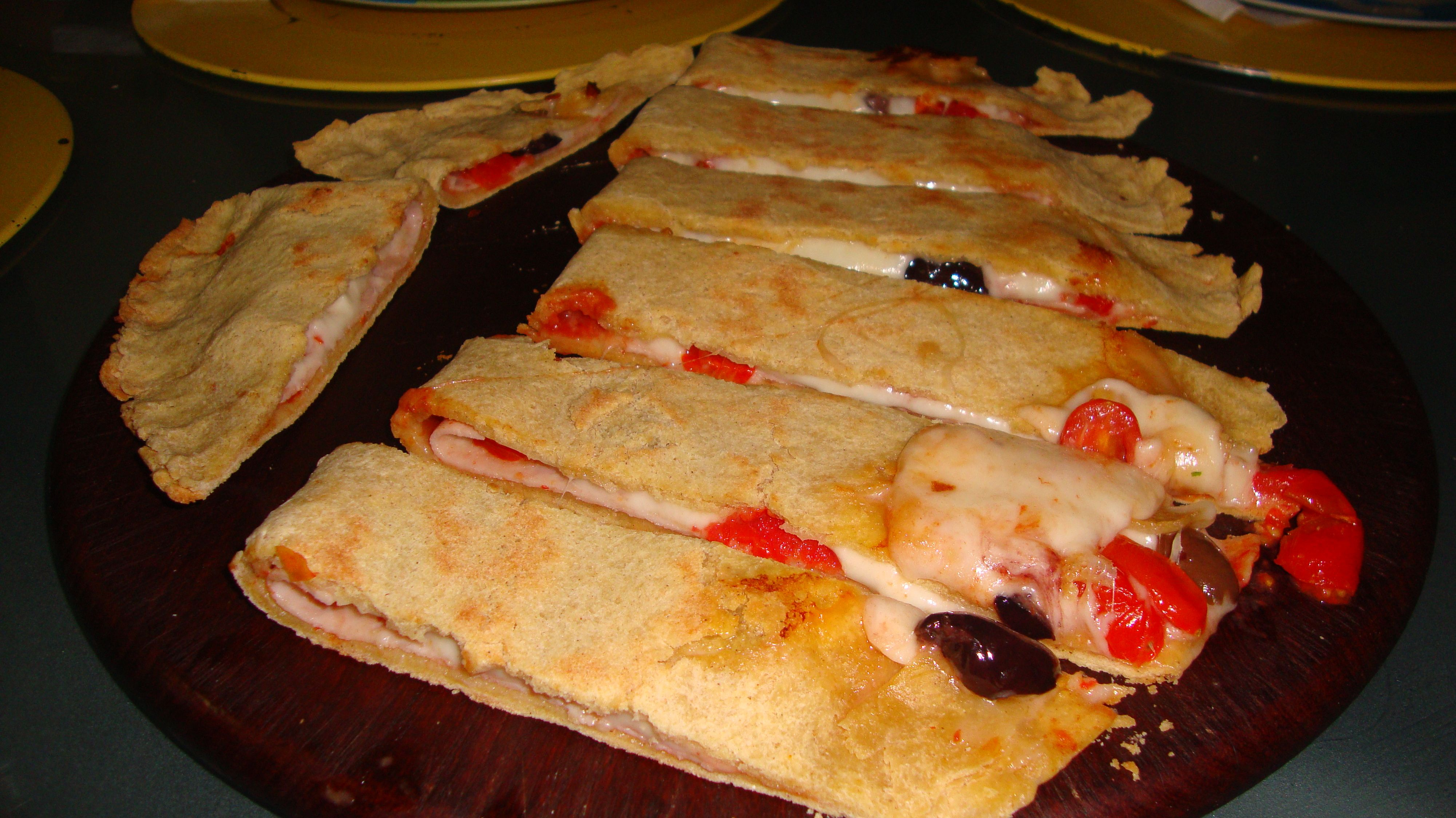 Calzone: Salsa de tomate, mozzarella, tomate bola natural, jamón, salami y aceitunas kalamata