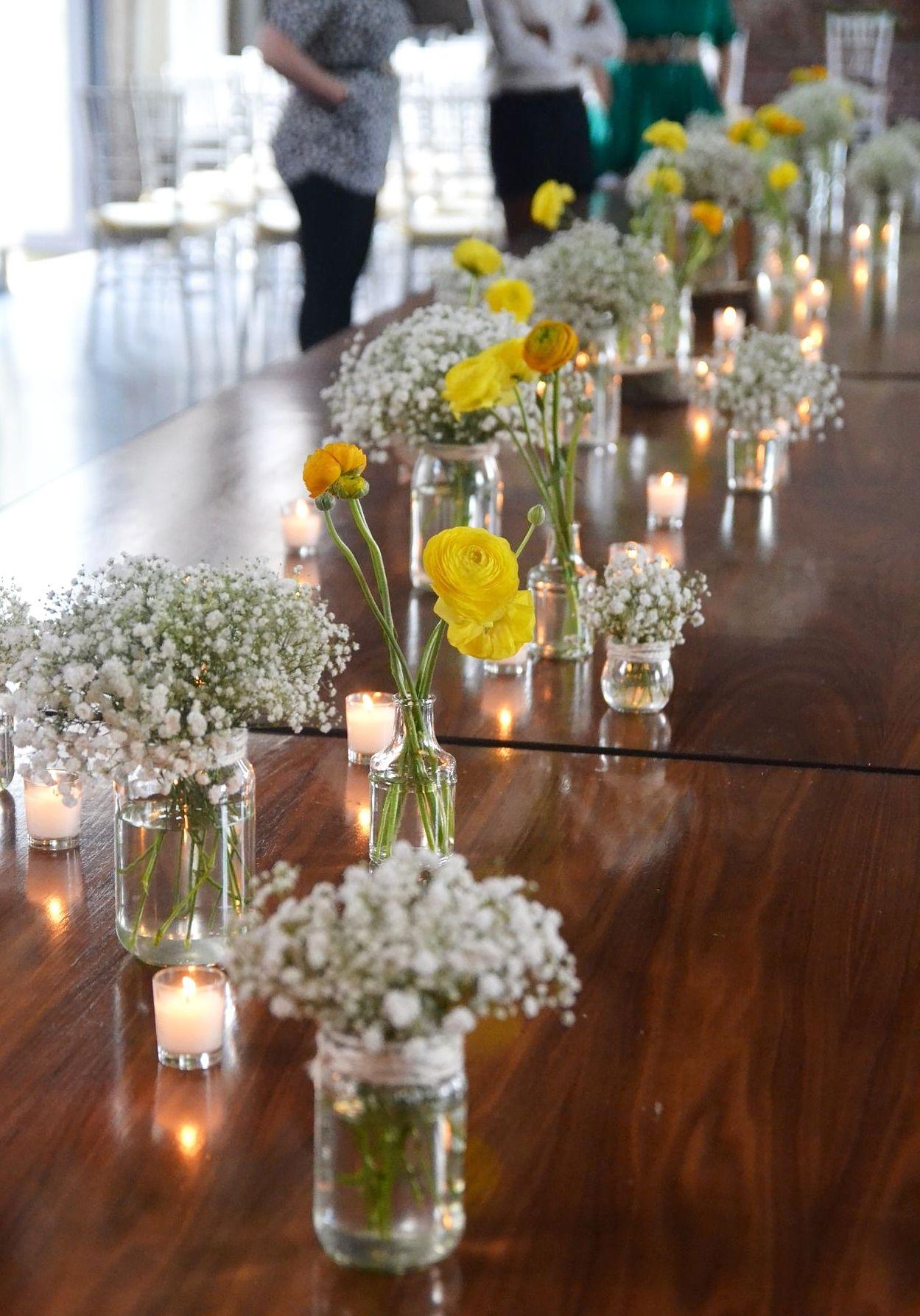Bright yellow spring time ranunculus blooms in bud vases and bright yellow spring time ranunculus blooms in bud vases and bunches of babys breath in jars reviewsmspy