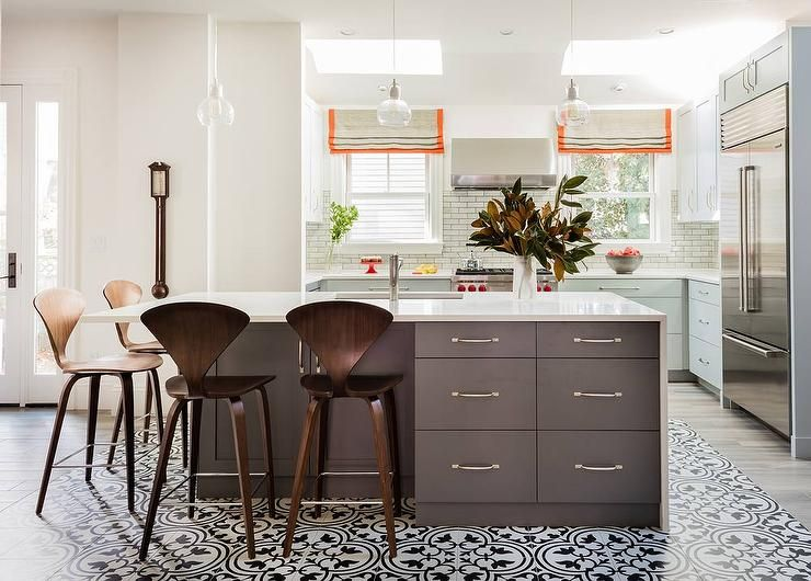 Three Glass Pendants Hang Over A Dark Gray Kitchen Island Wrapped With A White Quartz Waterfall
