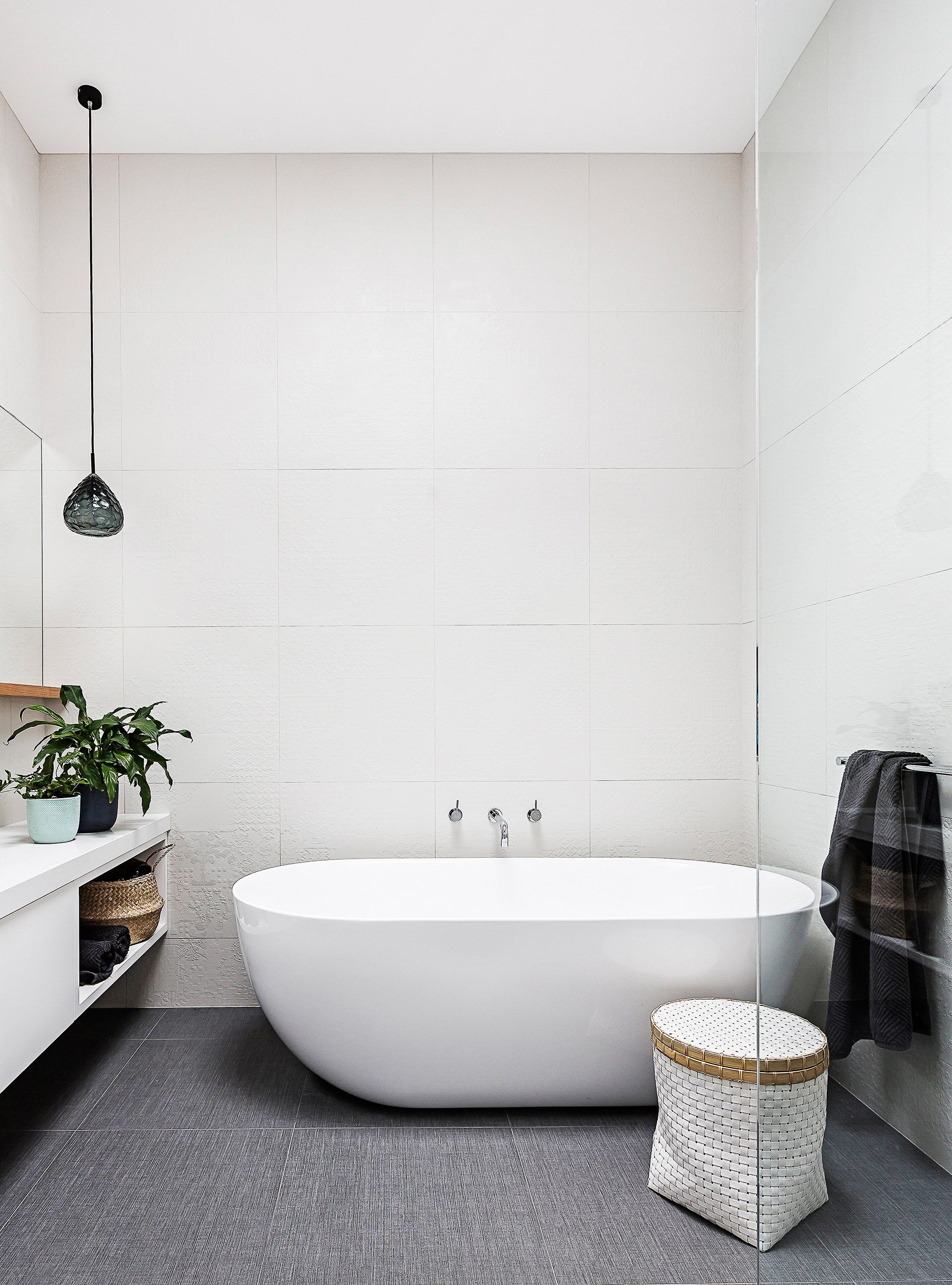 Floor and wall tiles with a subtle textural finish give this ...