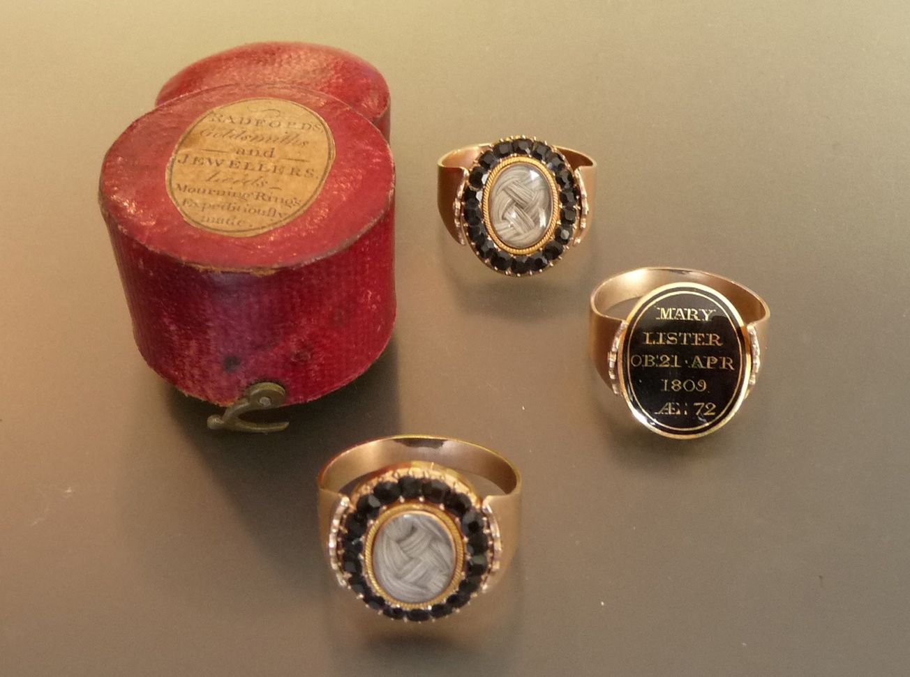 A Set of Three Mourning Rings, each encloses plaited hair within faceted jet on a swivel head, enamelled in black to the reverse to read 'MARY LISTER OB21 APR 1809 Ae: 72', in red cases, one with a paper label for Radfords goldsmiths and jewellers, Leeds