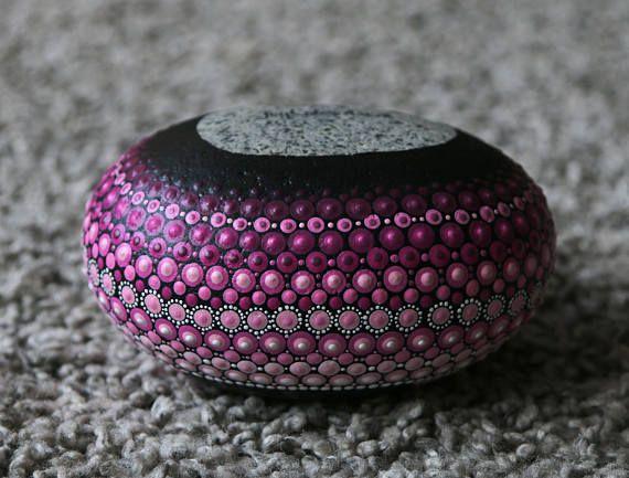 Mandala steen met onder andere roze acrylverf. Circa 11 bij 13.5 cm om een indruk van de grootte te geven. De steen is 1542 gram. Er staat een boeddha op geschilderd. De mandala stenen zijn afgewerkt met een laagje vernis maar kan alsnog niet gebruikt worden voor buiten, etc. Elke steen
