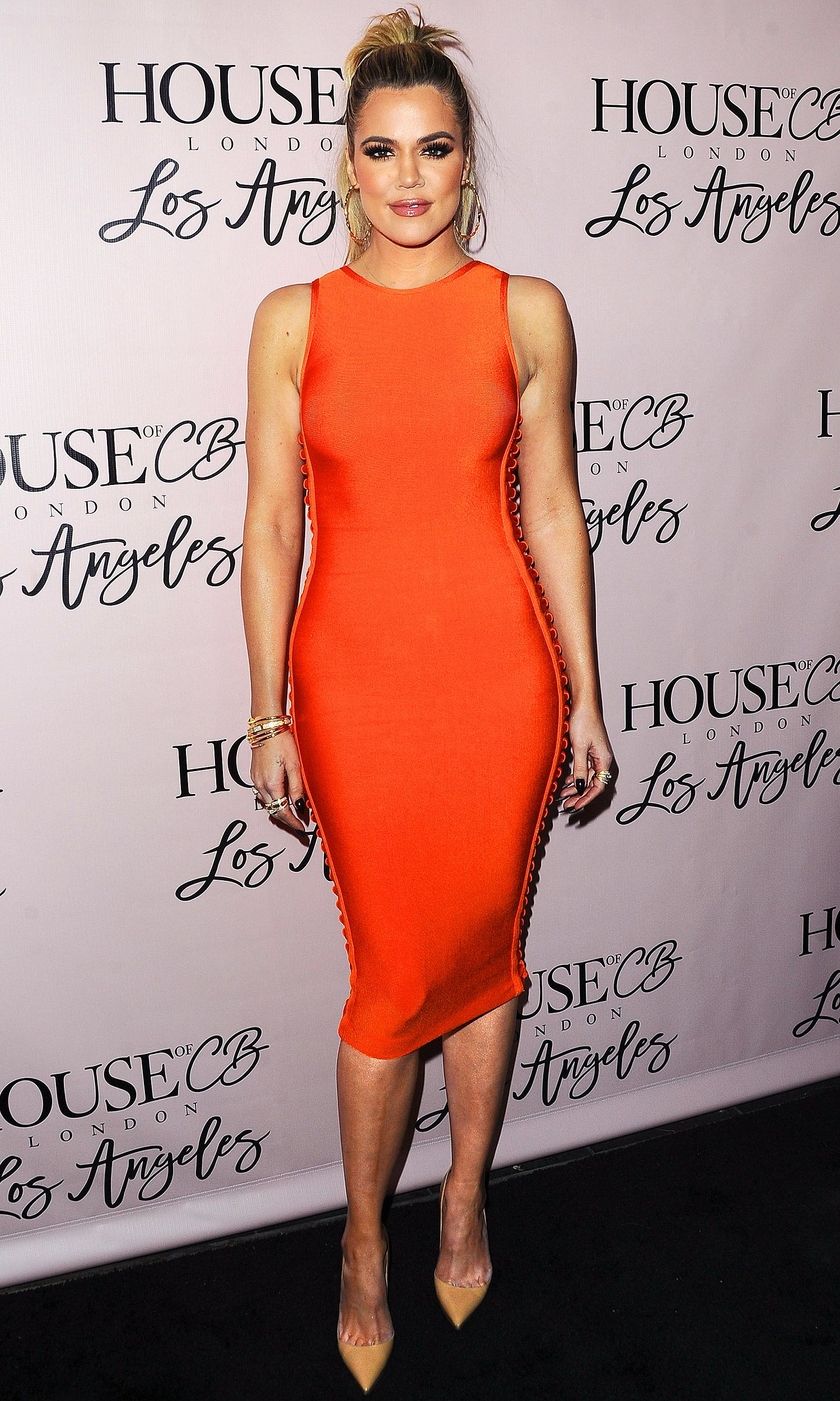 55ff3b26200 Khloe Kardashian in a tight orange House of CB midi dress and nude heels