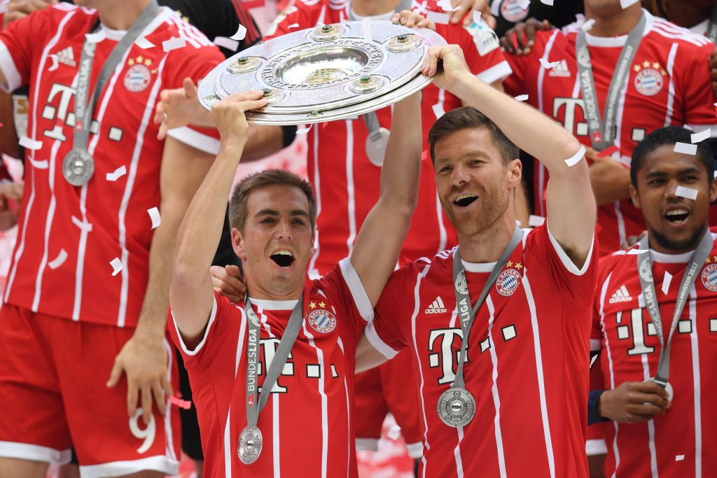 Philipp Lahm And Xabi Alonso Of Bayern Muenchen Lift The