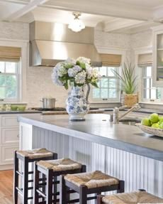 The kitchen island is finished with beadboard and topped with an extra-thick slab of soapstone.