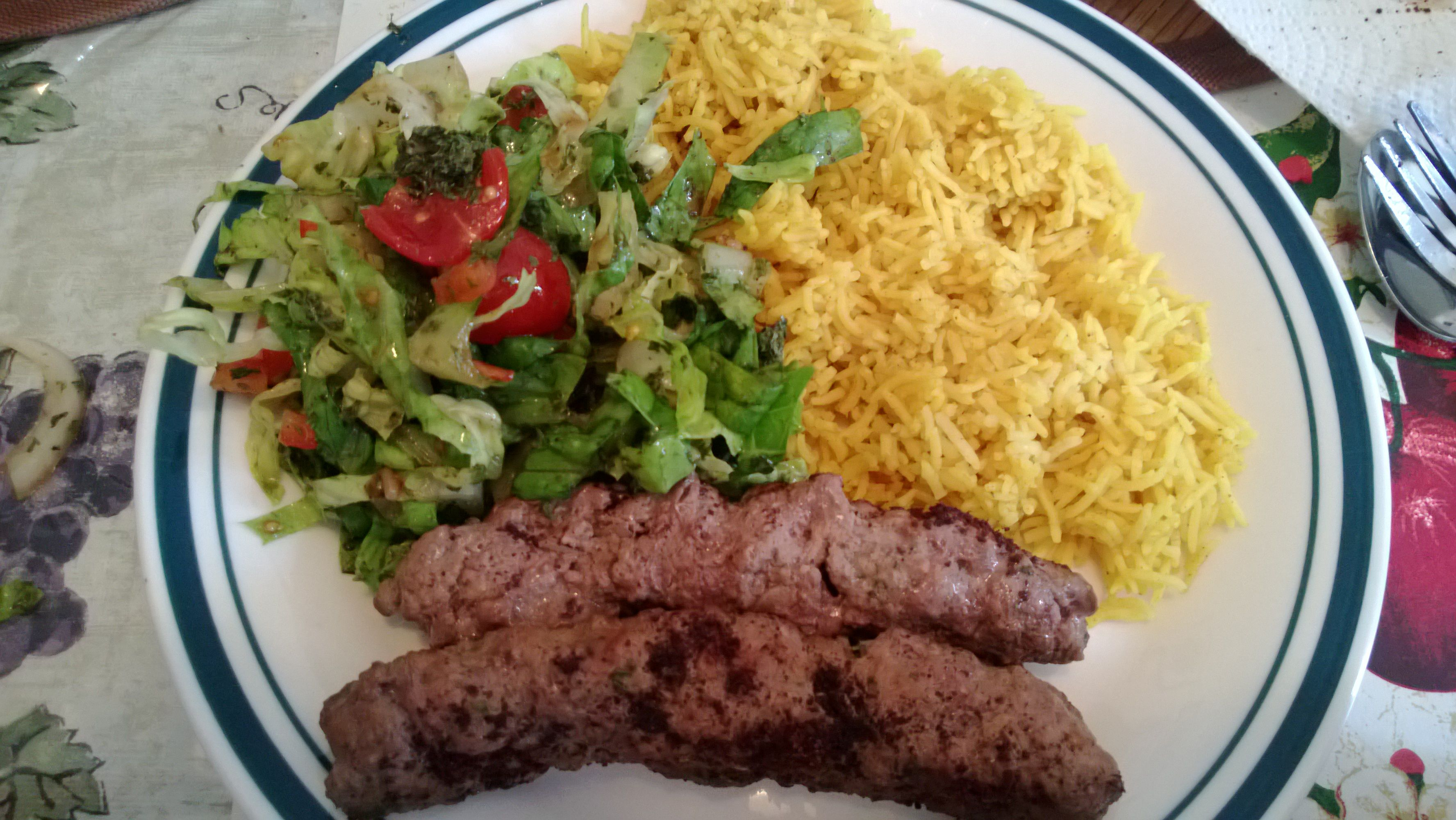 home made yellow rice , salad and grilled meat kofta.
