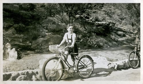 Shirley Temple rides a bike. In curlers.