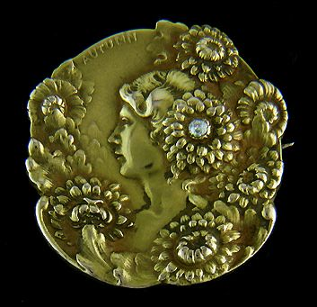 A beautiful Art Nouveau brooch celebrating autumn. A woman in profile is surrounded by a profusion of blossoming chrysanthemums. One of the chrysanthemums is set with a sparkling diamond. Created by Bippart, Griscom & Osborn in 14kt gold, circa 1900.