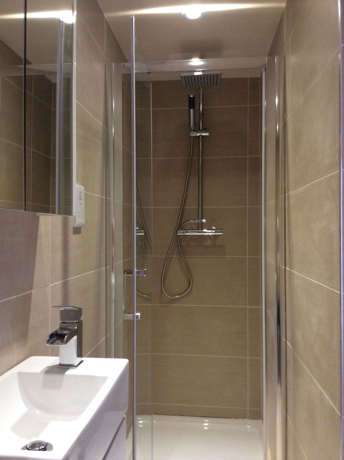The en suite shower room is fully tiled in dark cream for Small ensuite bathroom ideas