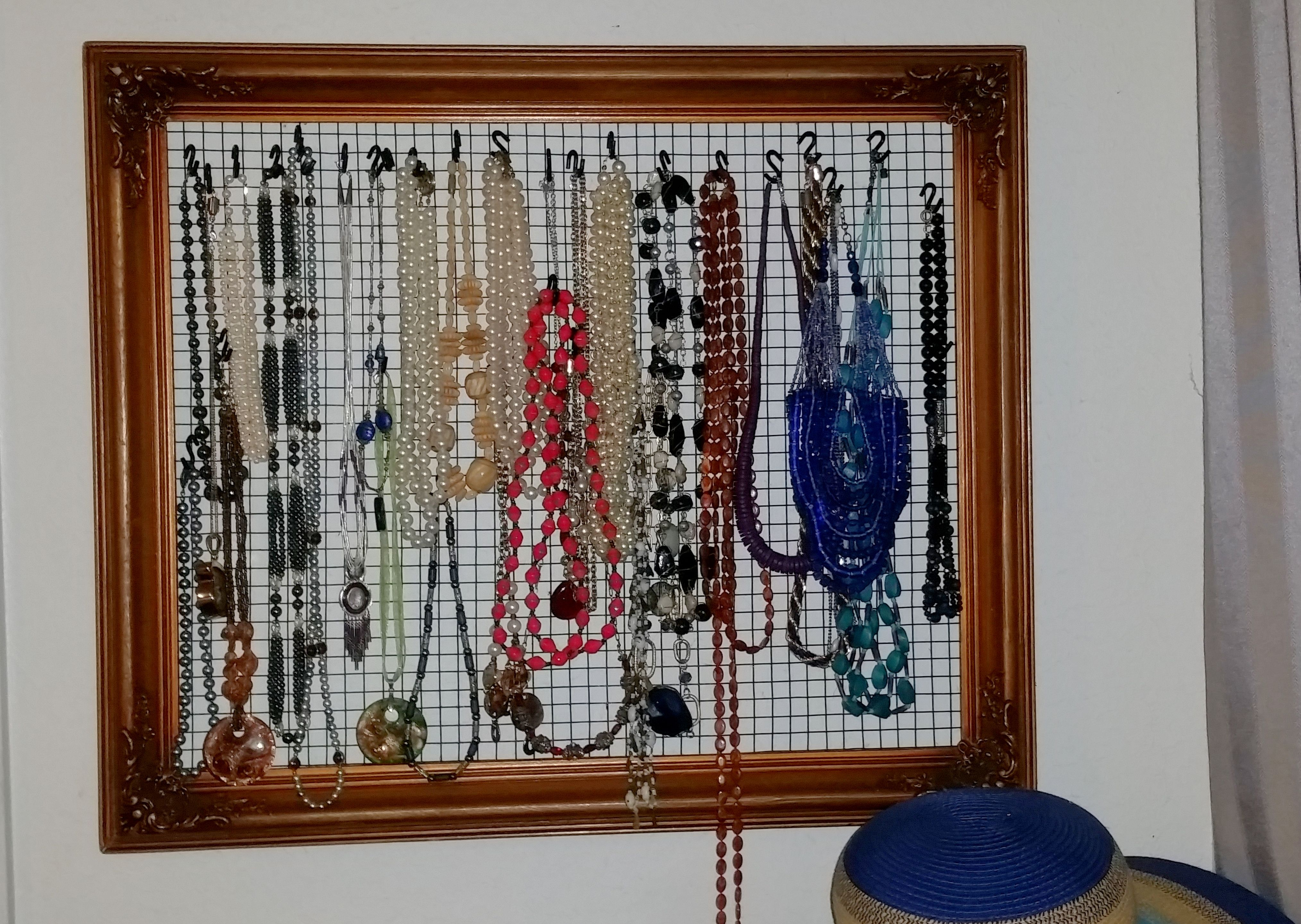 Jewelry rack from an old frame, hardware cloth, and s-hooks. This allows me to hang bulky necklaces and avoid the tangles of jewelry in the jewelry box.