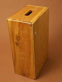 Apple Boxes are wooden boxes or crates of varying sizes with holes on each end used chiefly in film production. These boxes are specialized pieces of equipment belonging to the grip department, and should not be confused with simple crates or other boxes.