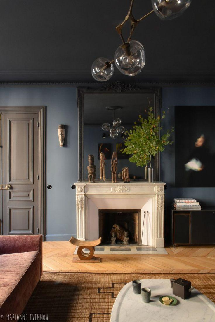 Moody and dark living room with dark blue walls, black trim and doors + light wood herringbone floors + large mirror over the fireplace + modern atom chandelier | Marianne Evennou #darkwalls