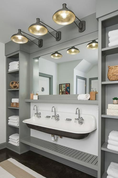 Gray built-in shelving units flank a vintage trough shared sink in a