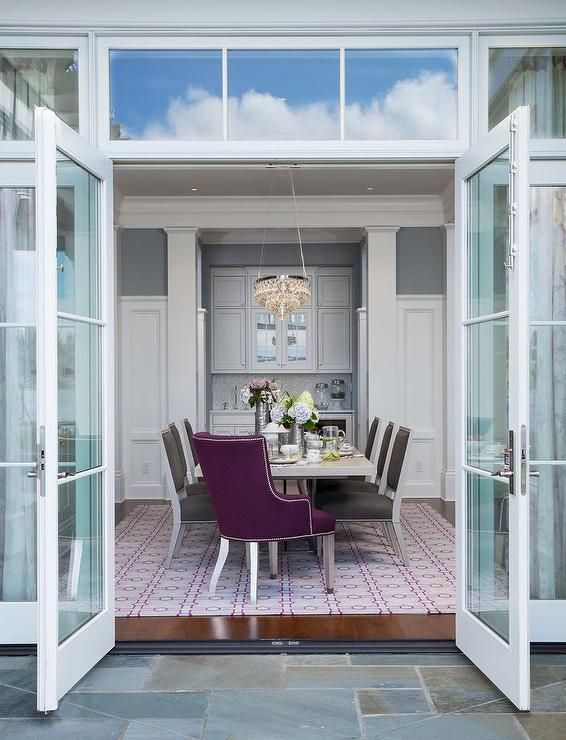 Glass Patio Doors Open To A Purple And Gray Dining Room Boasting An Oval Chandelier