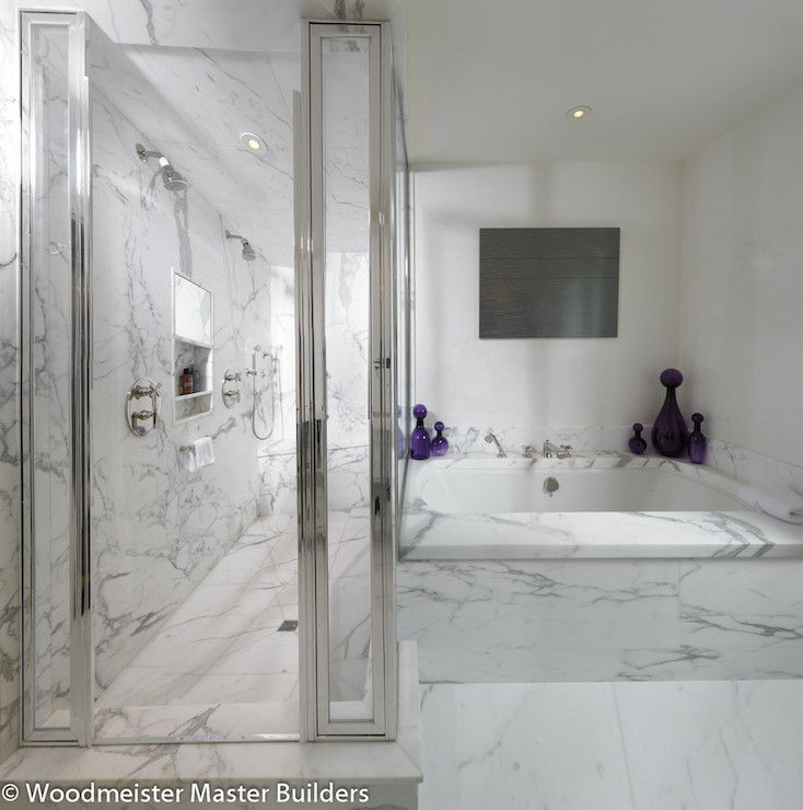 Spa like bathroom with large soaking tub framed by marble paneled ...