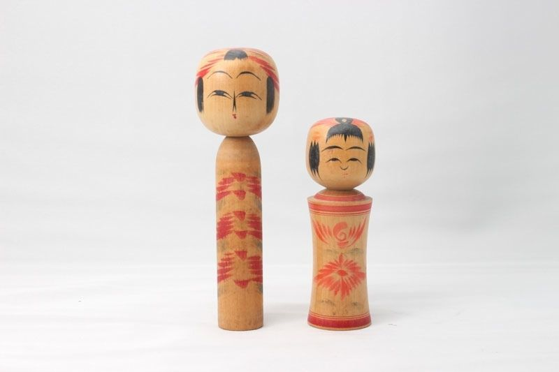 a pair of small dolls tallest about the same height as a iphone