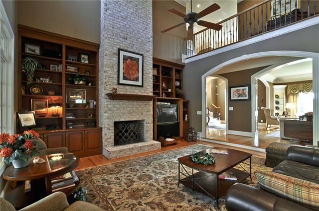 Two Story Great Room features Brick Fireplace and Built-in ...