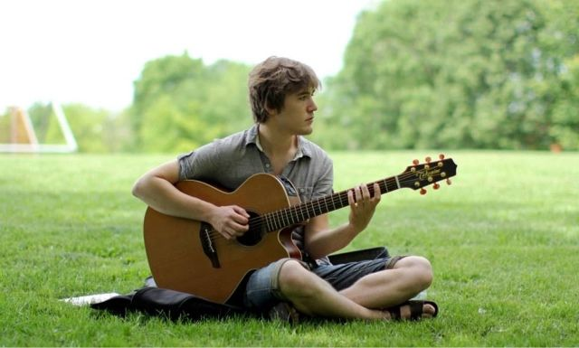 This Is A Picture Of Guy Playing Guitar On The Grass And Enjoying Nature