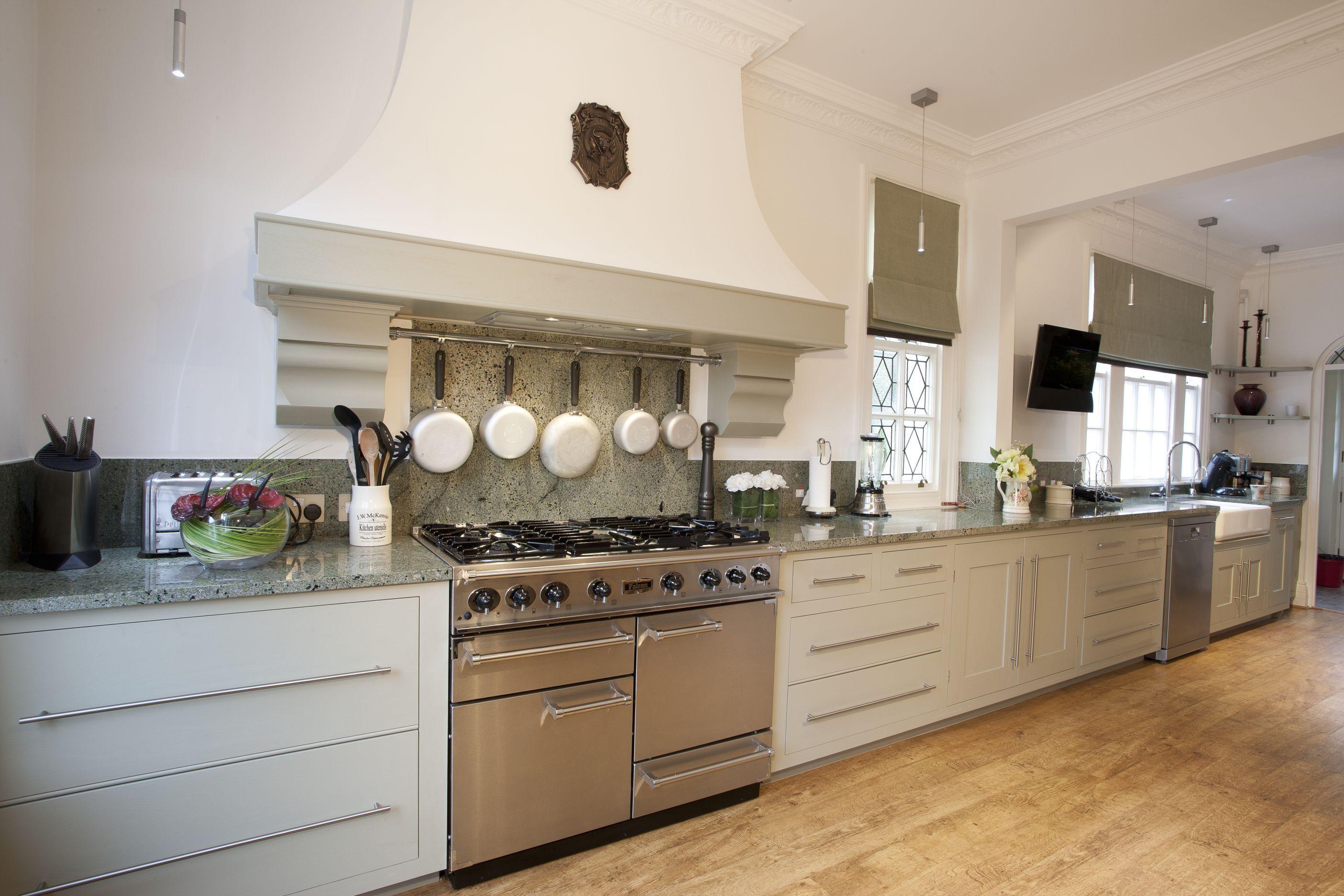 A modern long and open kitchen with white cabinetry. The ...