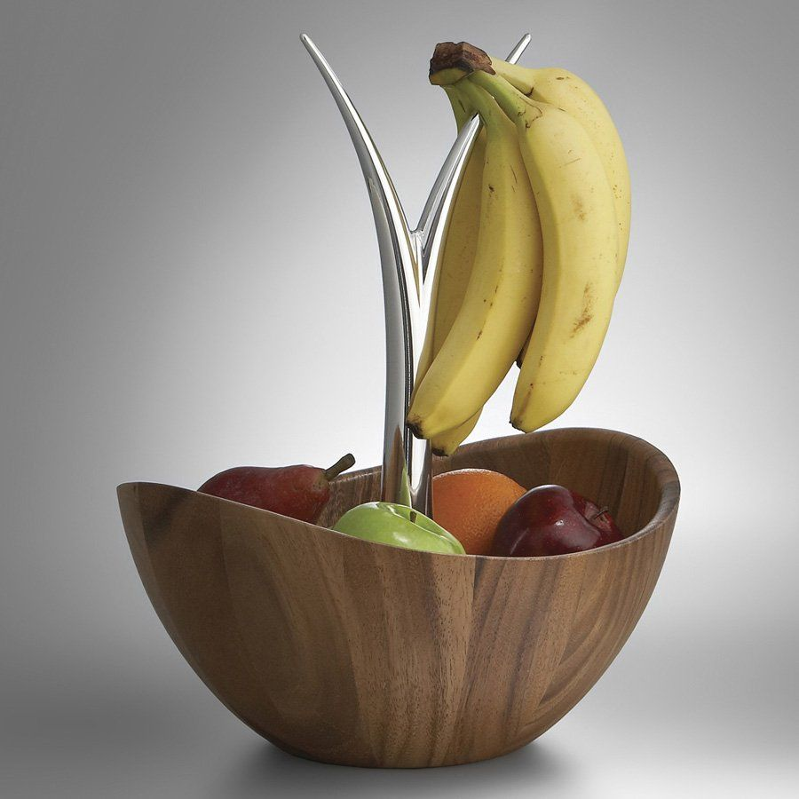 """The Fruit Tree Bowl adds a delicious sense of fun and jubilation to your kitchen or dining room. Fill the bowl with seasonal produce, and drape bananas or grapes over the Nambe alloy fingers for a celebration of wholesome goodness. The rich, natural wood tones make the fruit colors pop, and the upward gesture of the fingers—and of the shape of the bowl itself—give this unique piece an irresistibly playful spirit. Durable nambe alloy and acacia wood. 12"""" in length by 11-1/2"""" in width by 16""""…"""