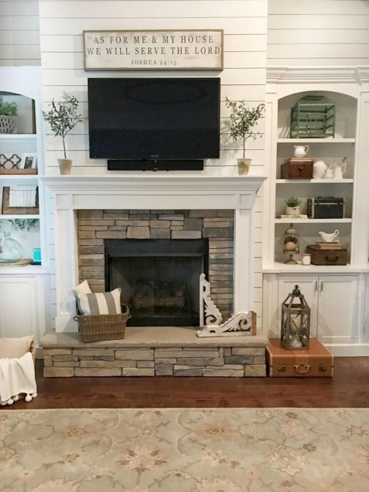 Shiplap walls, built-in shelving framing stone fireplace ...