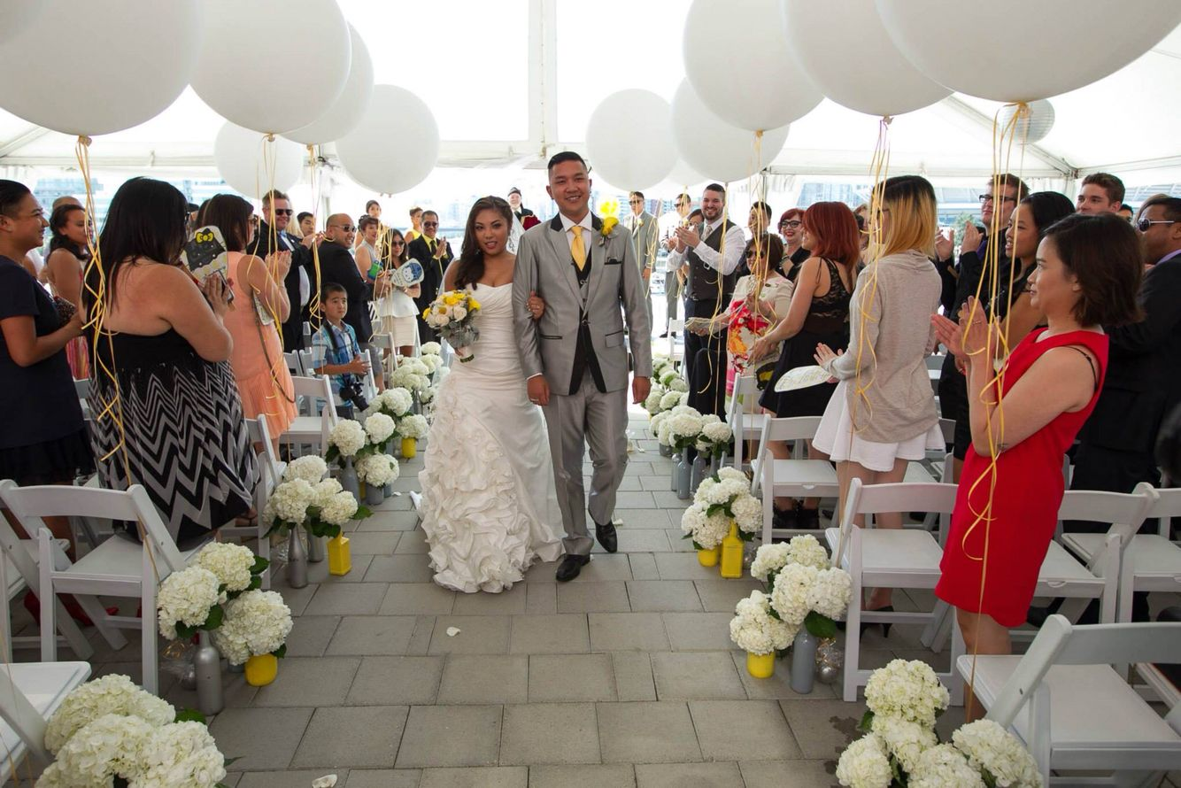 Ceremony aisle: white hydrangeas in painted bottles and large round balloons