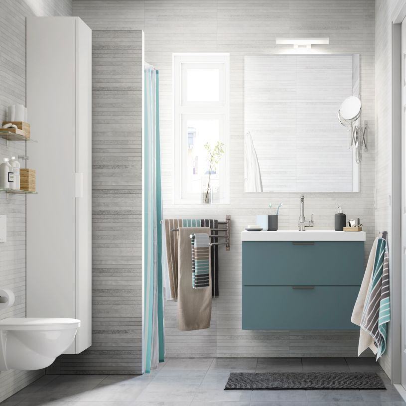 A light gray small bathroom with a white high cabinet, a mirror and