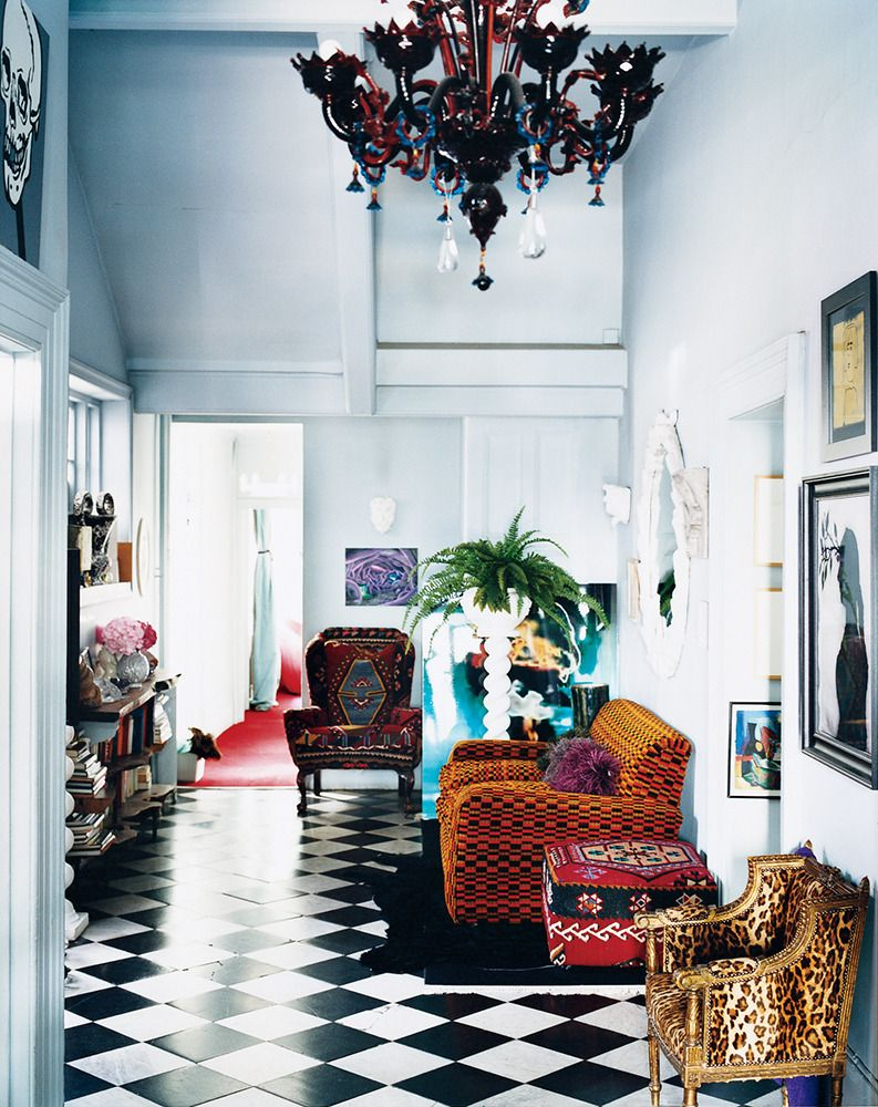 Eclectic elegance with black and white tiled floor jewel tone furniture and dramatic chandelier