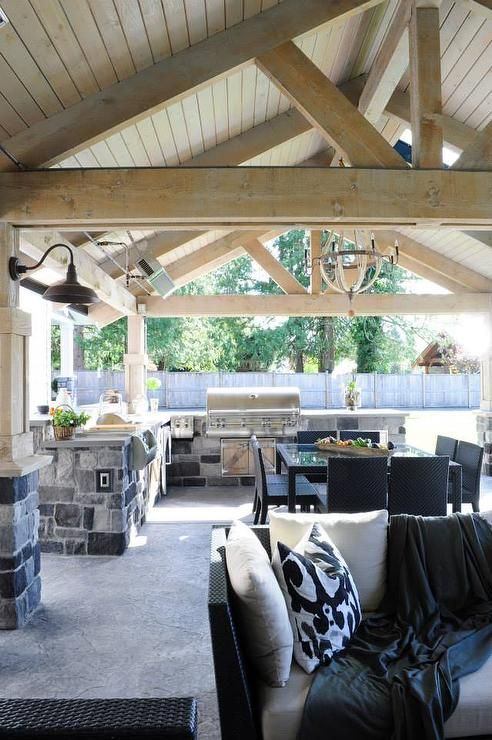 Covered Patio Features A Rustic Wood Truss Ceiling Over An L Shaped Gray  Stone Outdoor Kitchen Fitted With A Stainless Steel Bbq.