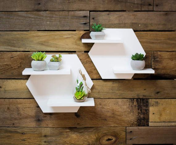 These hexagon shaped shelves are a delightful addition to your wall and perfect for displaying your plant collection or any knick knacks of your choosing. The clean white shelf set makes a versatile decorative accent for any room. Each adorable hexagon shelf is equipped with holes in the back so that they are ready to hang; this minimalist style, geometric inspired shelf will add character and delight to your space. This decoration is sturdy, useful, and oh-so-cute!  SIZE: Small - 12.5 wide…