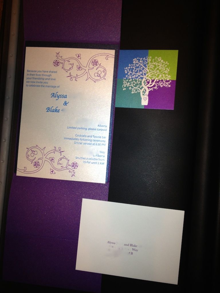This colorful wedding invitation featured peacock inspired purple, blue, aqua and green colors with a romantic carved heart and initials on a tree trunk.