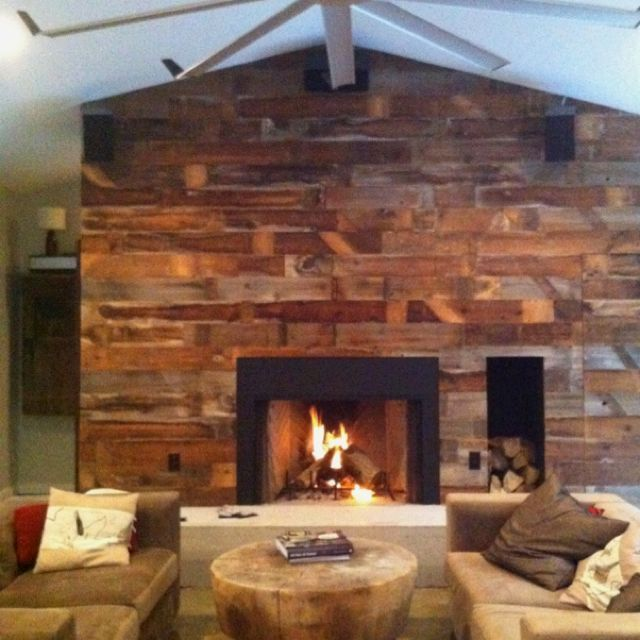 Old barnwood fireplace wall with wood storage and hidden powder room