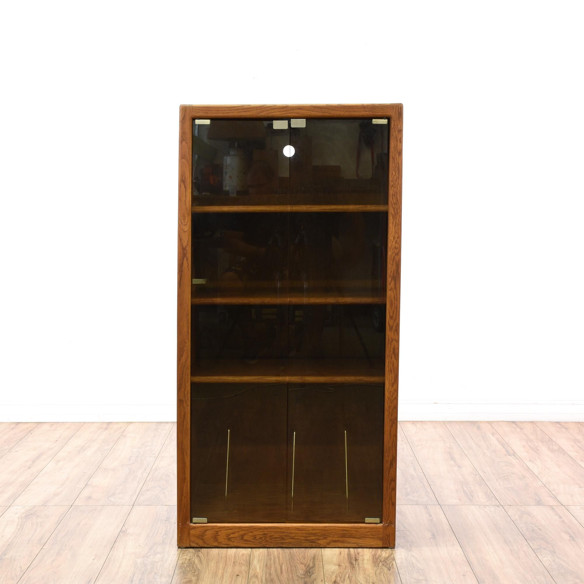This media cabinet is featured in a wood with a glossy oak veneer