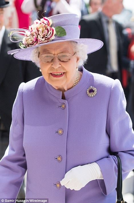Her Majesty wore a lilac suit and matching hat, topped with a broach and floral arrangemen...