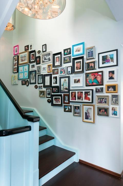 LEVENDE VEGG: Bildeveggen gjør at man ikke haster opp og ned trappa, men stopper opp litt. Komposisjonen vokser etter hvert som folk gifter seg og får barn. Foto: Espen Grønli