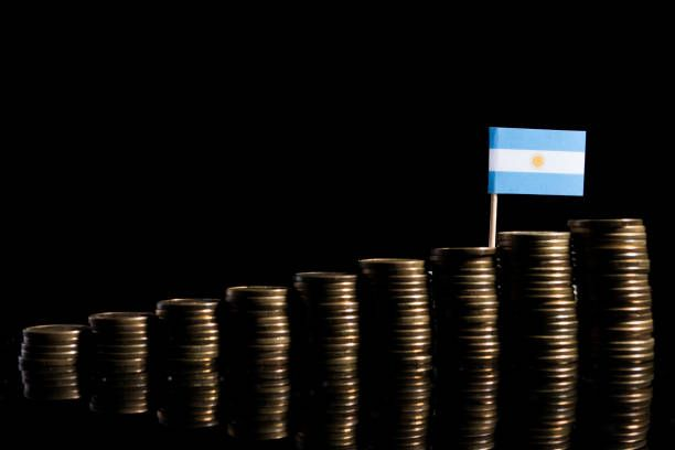 argentinian flag with lot of coins isolated on black background